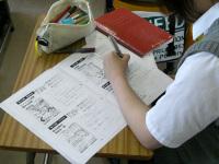 報告内容をメモする生徒